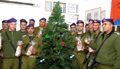 Soldati israeliani arabo-cristiani ricevono regali di Natale dal loro comandante (a destra) e dai loro compagni ebrei e beduini in una base nei pressi di Kerem Shalom, nel sud di Israele