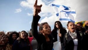Cittadini israeliani etiopi protestano a Gerusalemme contro discriminazioni e pregiudizi sventolando bandiere israeliane