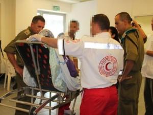 Infermieri della Mezzaluna Rossa palestinese portano una paziente all'ospedale da campo delle Forze di Difesa israeliane allestito la scorsa estate al valico di Erez fra Israele e striscia di Gaza