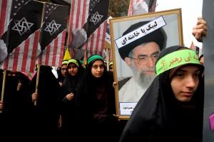 Manifestazione a Teheran. Sugli stendardi dietro al ritratto di Khamenei, un mix di bandiera americana, stella di David ebraica e svastica nazista
