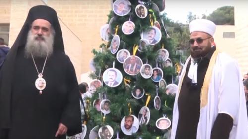 """L'arcivescovo Atallah Hanna e il muftì di Betlemme Abdel Majid Amarana posano nel campus di Abu Dis (Gerusalemme est) dell'Università palestinese Al-Quds a fianco dell'albero di Natale nazionalista"""" decorato con le immagini di """"martiri"""" palestinesi uccisi nei mesi scorsi mentre cercavano di assassinare cittadini israeliani"""