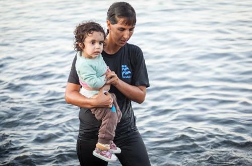 Tali Shaltiel, dottoressa israeliana di IsraAid, porta a riva un piccolo profugo siriano da un gommone approdato ad una spiaggia dell'isola greca di Lesbo