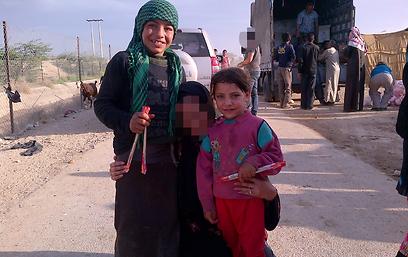 """""""Anat"""", al centro (col volto offuscato), in compagnia di piccoli profughi siriani"""