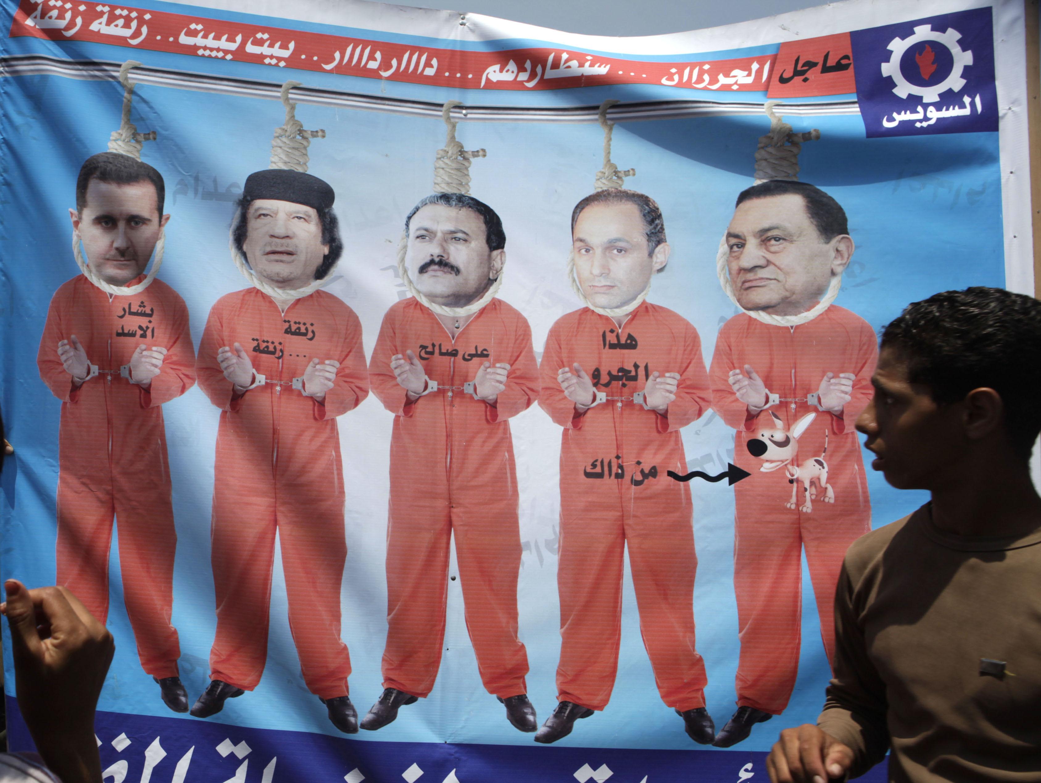 Piazza Tahrir, Cairo, 15 luglio 2011: da destra a sinistra, il presidente egiziano Mubarak (destituito 11 febbraio 2011), suo figlio Gamal, il presidente dello Yemen Ali Abdullah Saleh (destituito il 27 febbraio 2012), il capo della Libia Muammar Gheddafi (ucciso il 20 ottobre 2011) e il presidente siriano Bashar al-Assad in uniforme da carcerati