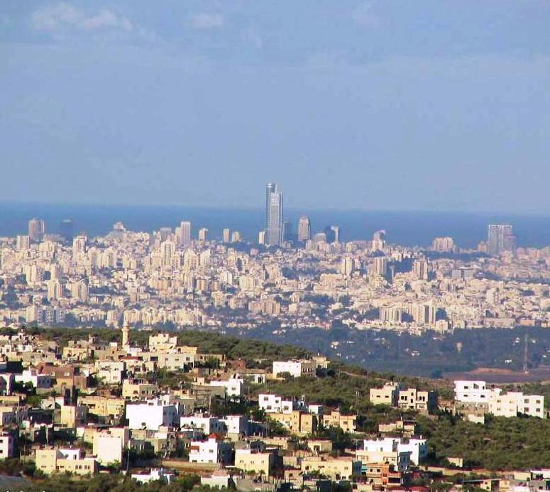In questa foto, scattata con un obiettivo da 58 mm, si vede in primo piano un villaggio di Cisgiordania che diventerebbe parte dello stato palestinese se Israele si ritirasse fino alla ex linea armistiziale pre-'67. Sullo sfondo: Tel Aviv e il mar Mediterraneo.