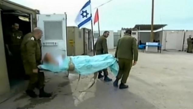 Soldati israeliani trasportano un ferito siriano ferito nell'ospedale da campo allestito in una località (non resa nota) sulle alture del Golan