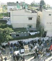 """8 luglio 2014 - Civili palestinesi riuniti come """"scudi umani"""" sopra e davanti alla casa a Khan Yunis usata come centro di comando da Odeh Kaware, a capo terrorista delle Brigate Izz al-Din al-Qassam (Hamas) – dopo che le Forze di Difesa israeliane avevano avvertito che l'avrebbero colpita"""