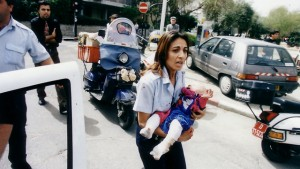 La foto che commosse Israele diciotto anni fa: l'agente Ziona Bushri porta fra le braccia la neonata Shani subito dopo l'attentato al Caffè Apropo