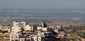L'aeroporto internazionale Ben Gurion visto da un villaggio palestinese di Cisgiordania. Sulla sinistra, il terminal e la torre di controllo; sulla destra, una pista. Sullo sfondo, sobborghi di Tel Aviv e il mar Mediterraneo (clicca per ingrandire)