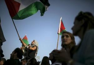 Cittadini arabi israeliani protestano in Piazza Rabin, a Tel Aviv, sventolando bandiere palestinesi