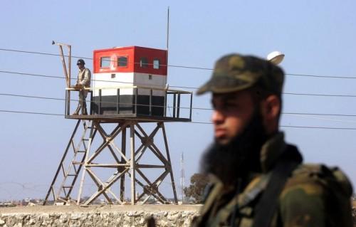 Un membro delle forze di Hamas sul versante palestinese della frontiera di Rafah. Sull'altro versante, un soldato egiziano sulla torretta di guardia