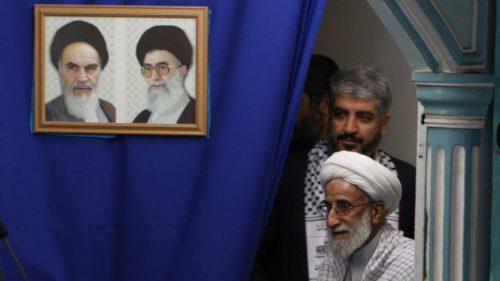 L'ayatollah Ahmad Jannati, accompagnato dal capo di Hamas Khaled Mashaal, arriva ad un cerimonia presso l'Università di Teheran nel febbraio 2009. Nei quadri, il defunto leader ayatollah Ruhollah Khomeini, a sinistra, e la Guida Suprema ayatollah Ali Khamenei