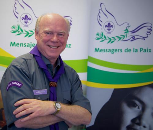 """Scott Teare, Segretario generale dell'Organizzazione Mondiale del Movimento Scout, fotografato avanti al poster """"Messaggeri di pace"""""""