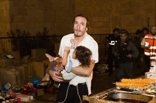 Un uomo ebreo porta un bambino ferito nell'attentato terroristico del 3 ottobre 2015 nella città vecchia di Gerusalemme